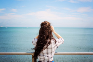 Teen girl with long brunette hair looking out to sea. Blue water and steel railings.