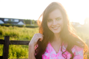 Backlit portrait of teen girl wearing bright pink patterned shirt. Green grass and fence in background.
