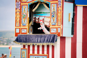Punch and judy show on beach. Red and white striped cabin