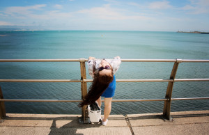 Teen girl leaning backwards on beach front railings. Blue sea and skies