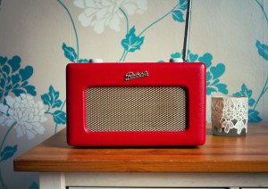 Red roberts vintage style radio with blue floral wallpaper background.