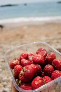 Punnet of strawberries with beach and sea in background