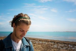 Teen boy wearing denim jacket on beach. Sunny day blue sky