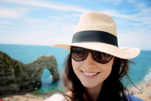 Girl wearing straw hat at Durdle Door beach in Dorset