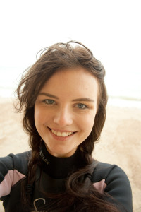 Girl with windblown hair. Black and pink wetsuit