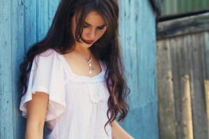 Teen wearing dragonfly necklace with boho style top