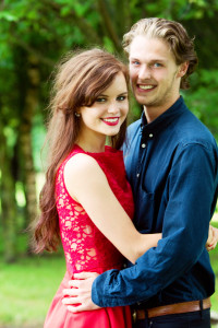 Young couple hugging. girl wears red dress from Jones & Jones London