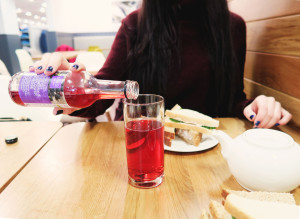 Girl pouring cranberry juice into tall glass