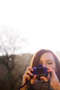 Teen girl looking at Canon compact camera