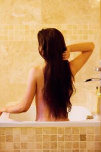 Girl with long brunette hair in bath