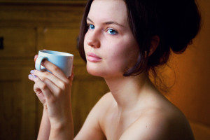 Teen girl with bare shoulders holding coffee cup