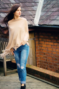 Teen girl wearing beige poncho with ripped jeans