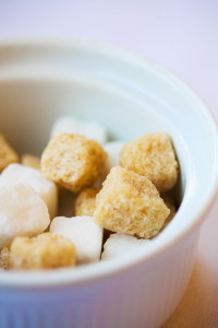 Brown and white sugar cubes in a dish