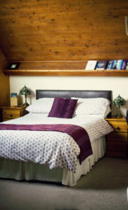 Bed against pine sloping ceiling