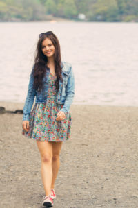 Teen girl wearing Liberty print floral dress and denim jacket walking by lake UK