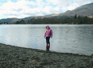 Young child in boots in lake