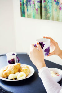 Girl holding purple flower print mug with croissant breakfast