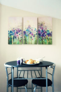 Triptych print of flowers over dining room set