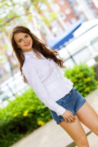 Smiling brunette teen girl wearing casual shorts outfit