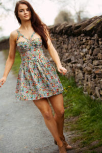 Girl in floral dress walking alongside stone wall