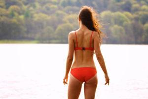 Teen girl wearing red Tringl bikini standing by side of lake