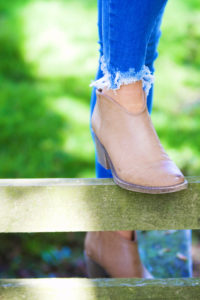 Frayed bottom blue denim jeans and western ankle boots