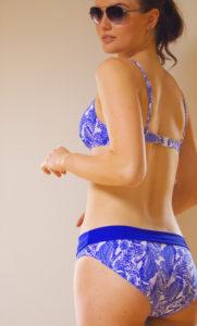 Teen looking back over shoulder wearing blue and white bikini