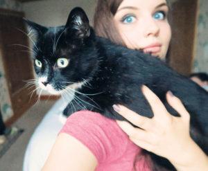 Girl holding black and white cat