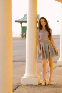 Smiling girl wearing grey lace skater dress