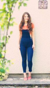 Teen girl. Denim summer outfit. White wall.