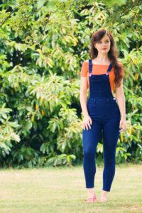 Teen girl wearing denim dungaress in garden