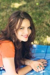Smiling teen girl lying on blanket in garden
