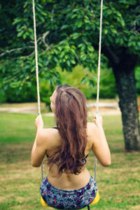 Teen girl on swing wearing bikini
