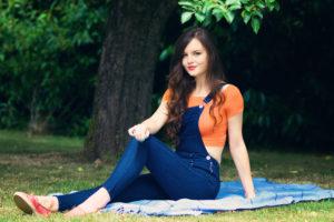 Teen girl sitting on picnic blanket