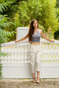 Teen girl wearing cropped top and culottes outfit.