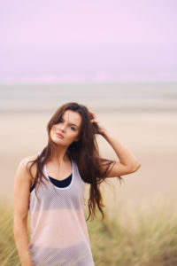 Brunette girl messing with long hair. Beach background