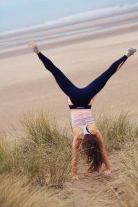 Girl doing cartwheel on top of sand dune.