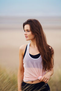 Girl with long brunette hair wearing pink mesh workout vest. Beach background.