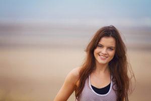 Smiling brunette girl. Beach background.