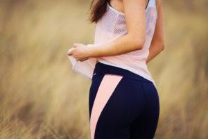 Girl wearing black and pink exercise leggings. Sand dune background