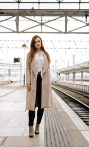 Girl on train station platform wearing jeans, long coat and beige boots.