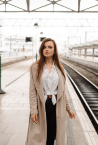 Girl standing on train platflorm wearing jeans and white shirt knotted at waist.