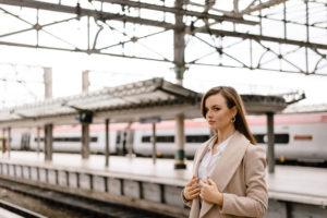 Girl wearing long beige coat standing on platform at train station Manchester England.