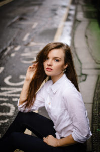 Girl sitting at side of road wearing white shirt and jeans. Long brunette hair.