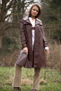 Girl wearing long brown leather coat over white shirt