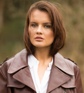 Brunette model wearing white shirt and brown leather coat
