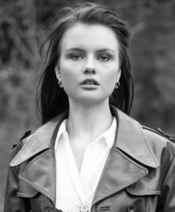 Black and white portrait of girl wearing white shirt and leather coat.