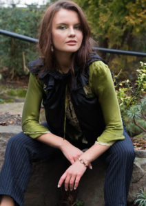 Girl wearing green top and black pinstripe trousers.