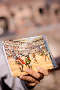 Postcards showing fighting at Colosseum Rome Italy. Hand holding postcards.