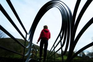 Girl stood on bridge with metal spiral detail.